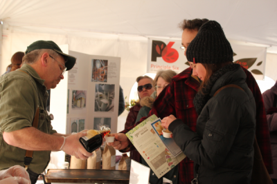 Customers tasting maple syrup from P6 member Maple Valley at the P6 tailgate party hosted by Viroqua Food Co-op in Viroqua, WI