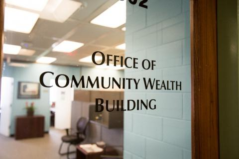"Glass office door with ""Office of Community Wealth Building"" lettered"